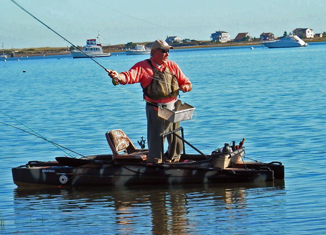 Fly fisherman casting standing in his stable kayak