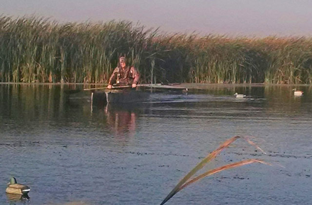 duck-hunter-in-camo-kayak-with-decoys-floating-around
