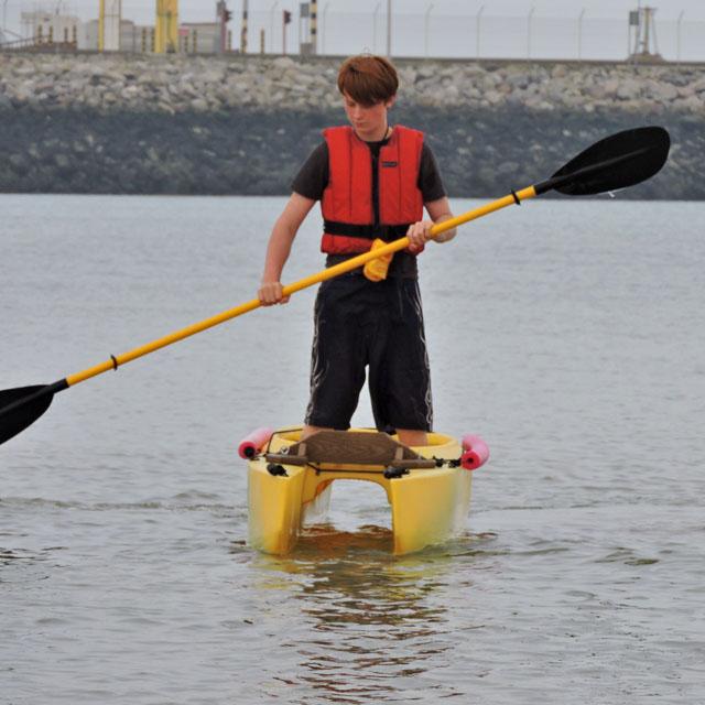 boy-paddling-standing-in-fishing-kayak