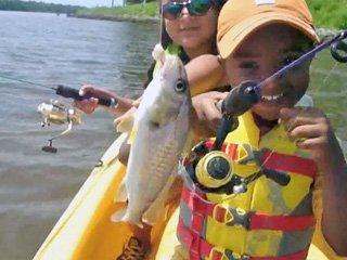 Young boy shows his father the fish he caught on board a WAvewalk 500 kayak