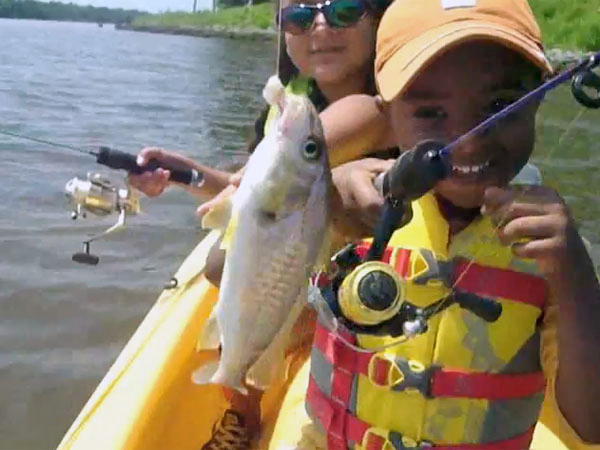 Two_kids_enjoying_the_fish_they_caught_in_their_father's_kayak