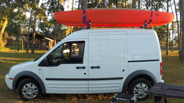 fishing kayak attached on top of vehicle