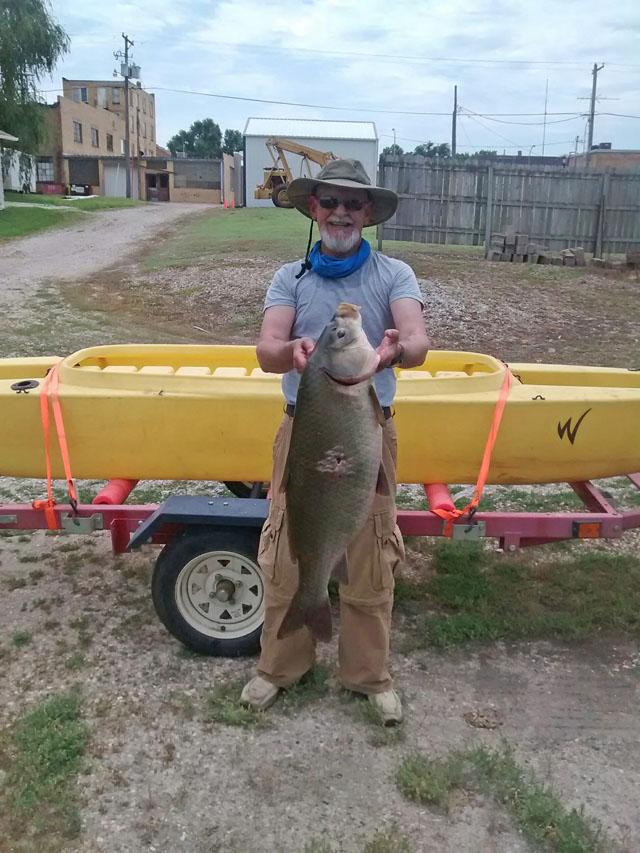 bow-fisherman-showing big-carp-caught-standing-in-kayak