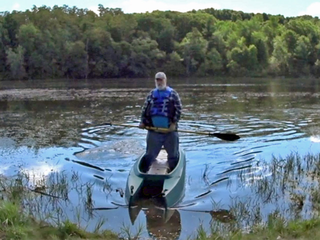 big and heavy 300 lbs fisherman paddling standing in his Wavewalk 700 fishing kayak