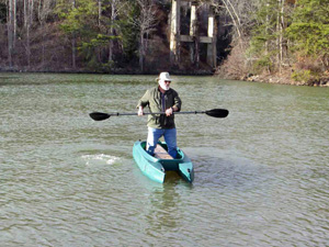 big and heavy fisherman paddling standing in his Wavewalk 700 fishing kayak