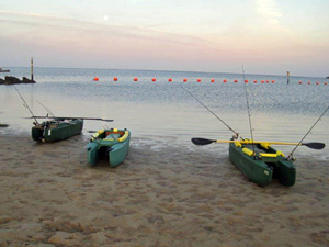 Three elderly fishermen's kayaks on the beach