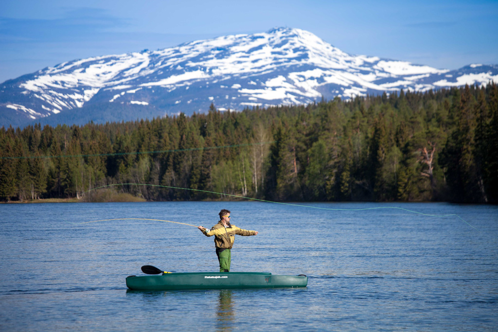 Christer standing in his kayak and fly fishing