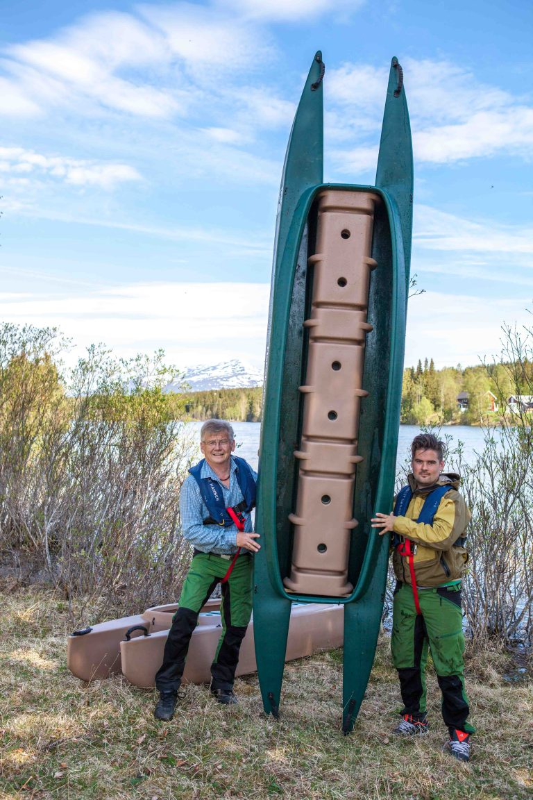 Two kayakers holding their Wavewalk 700 tandem kayak