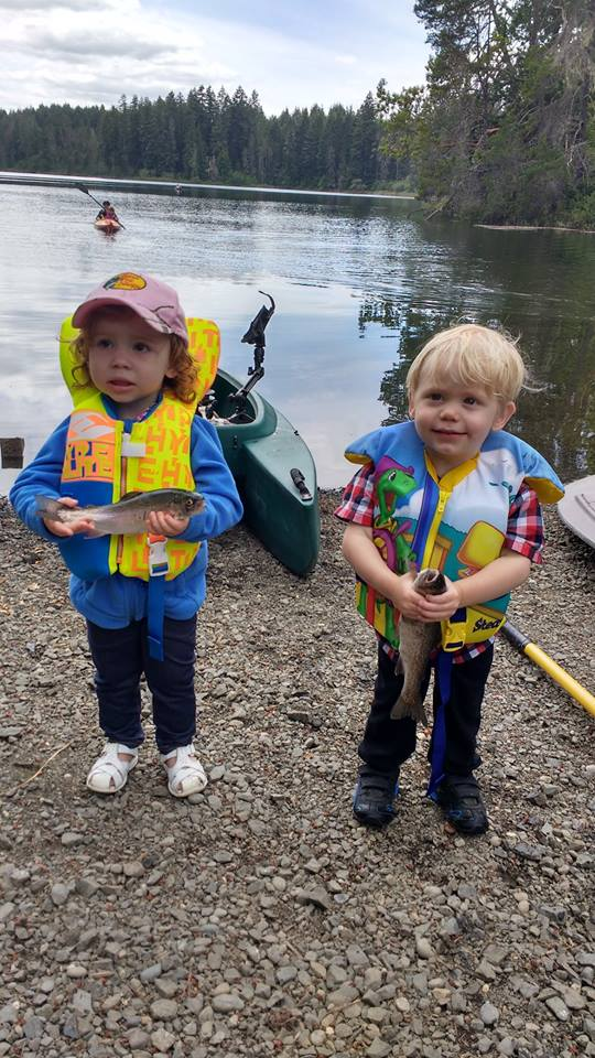 two small kids showing their first fish