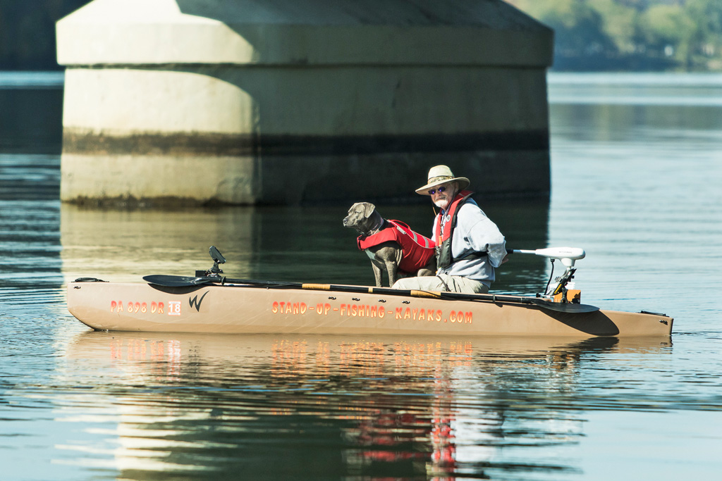 fisherman-driving-electric-fishing-kayak-with-dog-on-board-05-1024