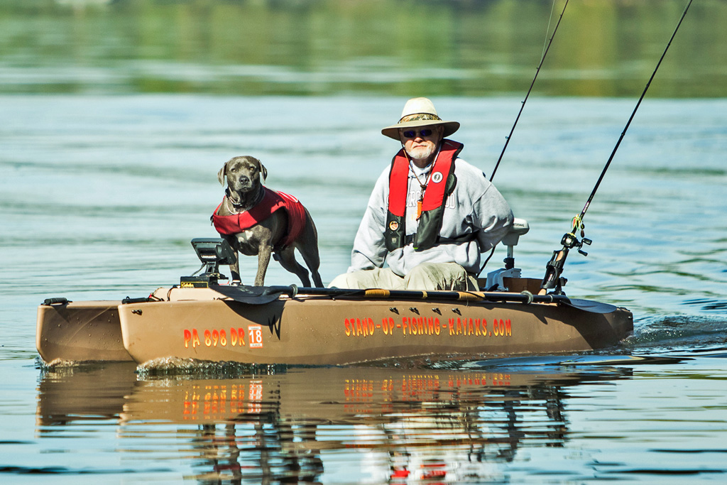 fisherman-driving-electric-fishing-kayak-with-dog-on-board-06-1024