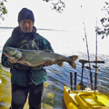 Ontario kayak angler showing his catch - big fish! Staning next to his electric fishing kayak