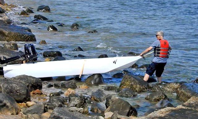 launching an ultralight skiff in a rocky beach