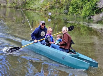 two parents and two children in their tandem fishing kayak