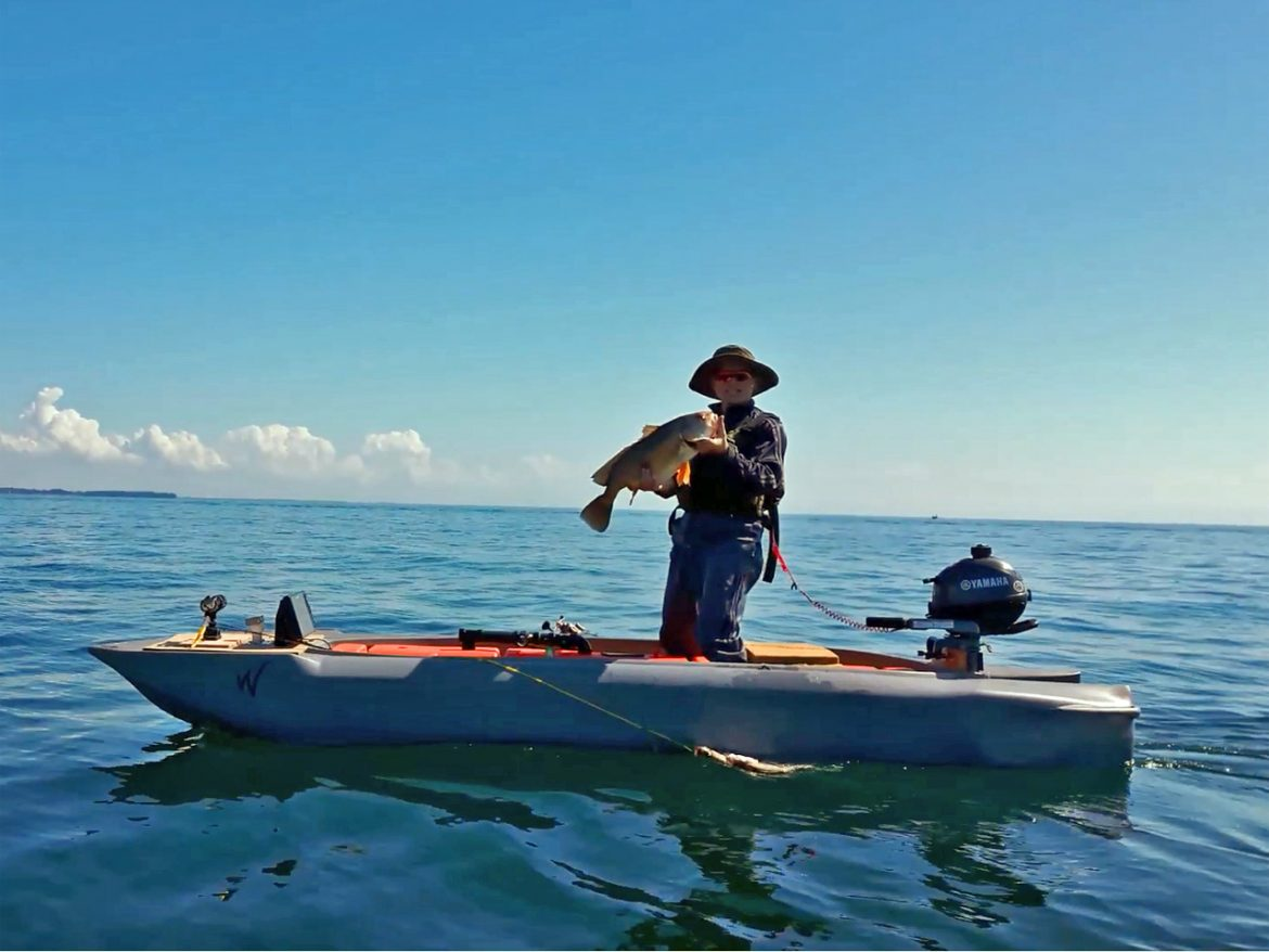 fisherman standing in his motor kayak and holding a big fish he caught from a motor kayak in a big lake