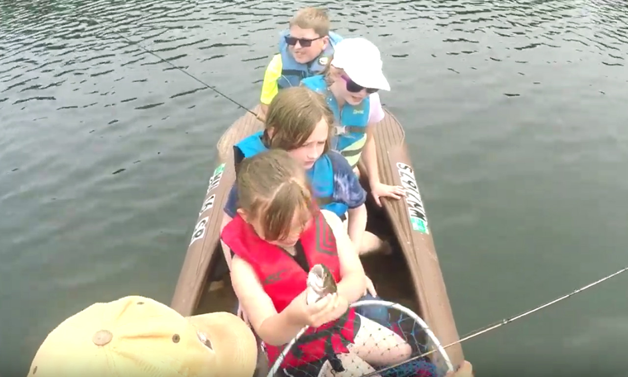 4 kids fishing out of a Wavewalk S4 kayak with one adult on board
