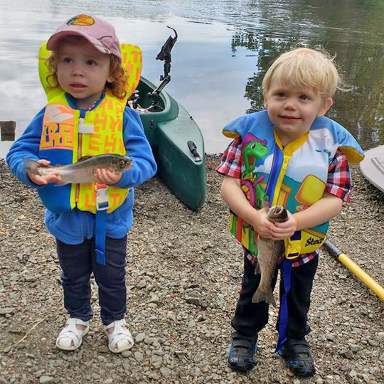 Two kids showing the fish they caught on board the kayak