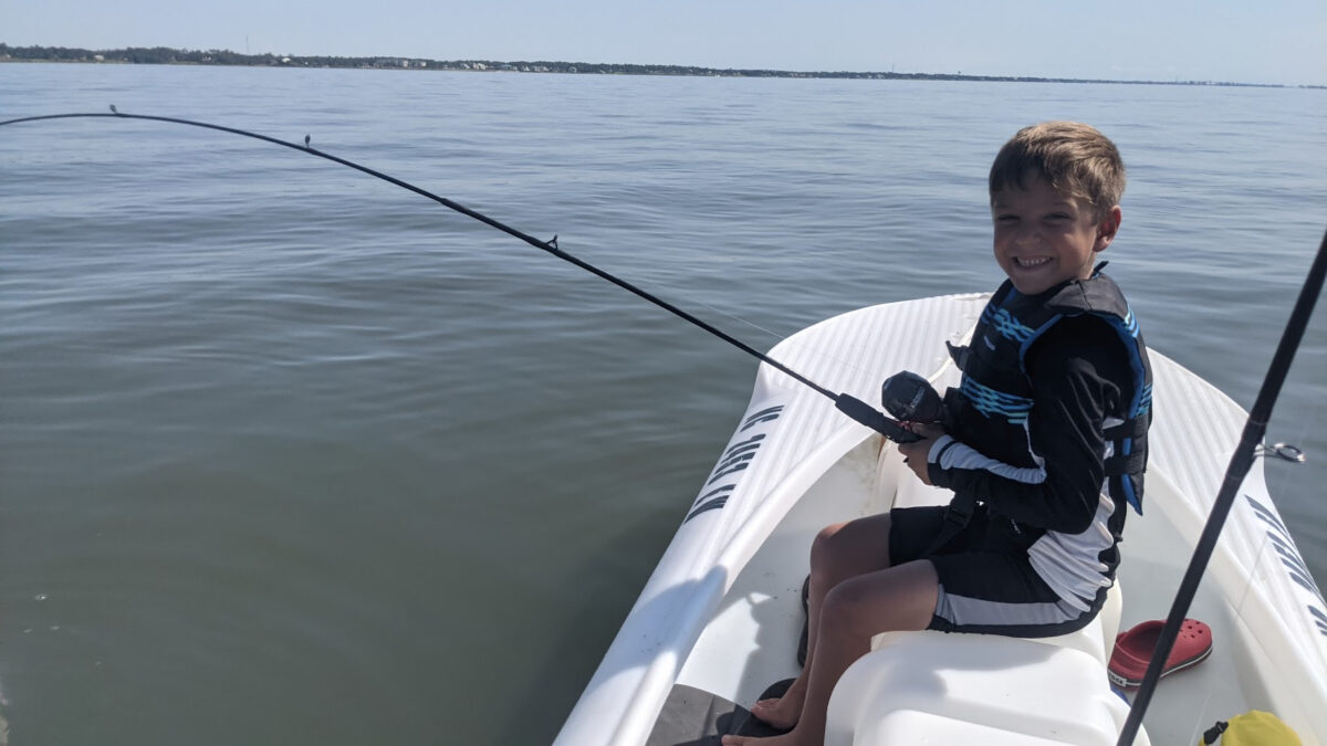 boy fishing out of hs dad's S4 microskiff